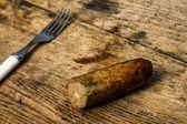 Widelec i kiełbasa na drewnianym stole — Zdjęcie stockowe