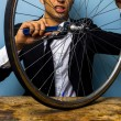 Man in suit trying to fix a bicycle tyre — Stock Photo #29971539