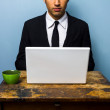 Businessman having coffee and working on laptop — Stock Photo