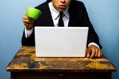 Businessman is surprised and nearly spills coffee on notebook — Stock Photo