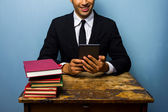 Businessman with books and e-reader — Stock Photo