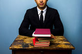 Businessman with stack of books — Stock Photo