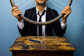 Man in suit trying to fix a bicycle tyre — Stock Photo
