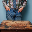 Man at desk with hands in pockets — Stock Photo