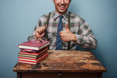 Geek man giving thumbs up at books — Stock Photo