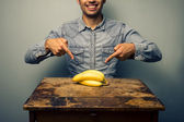 Man pointing at bananas at old desk — Stock Photo