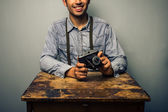 Hipster with vintage camera at old desk — Stock Photo