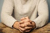 Muž se sepjatýma rukama, sedící u stolu — Stock fotografie
