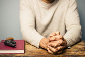 Praying man with a gun and important book — Stock Photo