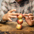 Man trying to balance apples on top each other — Stock Photo