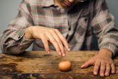 Man spinning an egg on the table — Stock Photo