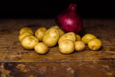 Potatoes and onion on wooden surface — Stock Photo