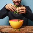 Happy man tossing salad — Stock Photo