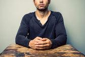 机に座っている折られた手を持つ男 — ストック写真