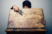 Student at school desk with gun — Stock Photo