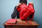 Student trying to find something in his bag — Stock Photo
