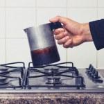 Man's hand placing espresso maker on stove — Stock Photo #30426887