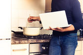 Man following recipe on his laptop computer — Stock Photo