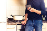 Man with digital reader in kitchen — Stock Photo