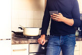 Man cooking and reading on his e-reader — Stock Photo