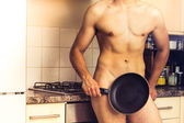 Naked chef standing by the stove with frying pan — Stock Photo