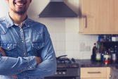 Happy young man in tidy kitchen — Stok fotoğraf