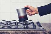 Man's hand placing espresso maker on stove — Foto Stock