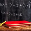 Books and chalk by blackboard with equation — Stock Photo