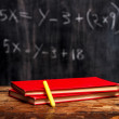 Books and chalk by blackboard with equation — Stockfoto
