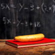 Banana and book by blackboard with equation — Stockfoto
