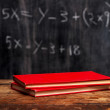Books by blackboard with equation — Stock Photo