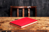 Closed book on desk by blackboard — Stock Photo