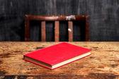 Stängd bok på skrivbord av blackboard — Stockfoto