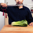 Silly man cutting lettuce with sword — Stock Photo