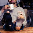 Man with worn out socks having coffee in kitchen — Stock Photo