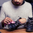 Man is polishing his boots — Stock Photo