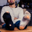 Man with worn out socks relaxing in kitchen — Stock Photo
