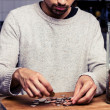 Man counting his money in kitchen — Stockfoto