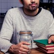 Man with jam jar and stack of books — Stockfoto