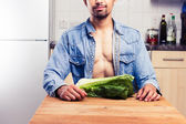 Sexy man in kitchen with lettuce — Stock Photo