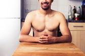 Naked man sitting in his kitchen — Stock Photo
