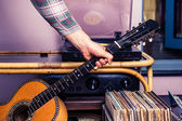 Hand picking up guitar next to box of vinyl — Stock Photo