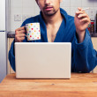 Man in robe working from home and smoking — Stock Photo