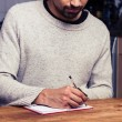 Young man writing in kitchen — Stock Photo