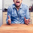 Screaming man gesturing with hands in his kitchen — Stock Photo