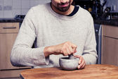 Muž v kuchyni je mletí koření — Stock fotografie