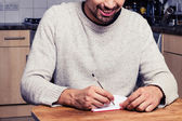 Smiling young man is writing in his kitchen — Stock Photo