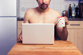Naked man at home with laptop and coffee — Stock Photo