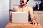 Young naked man watching pornography in his kitchen — Stock Photo