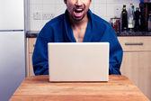 Genç adam onun laptop bir şey izlerken heyecanlı — Stok fotoğraf